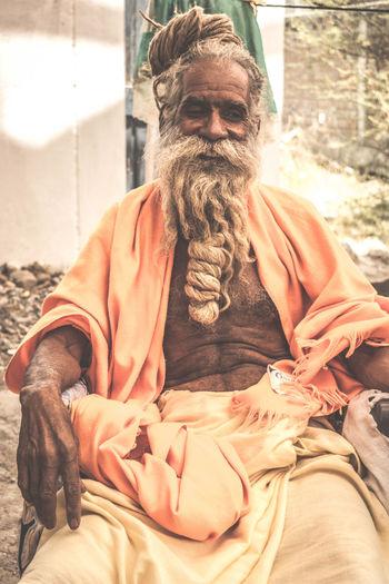 Bearded sadhu sitting outdoors