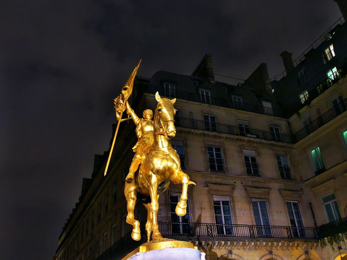 Low angle view of statue against illuminated city at night