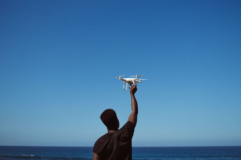 Rear view of man holding drone against blue sky