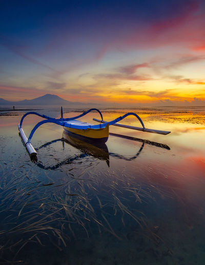 Boat moored at beach during sunset