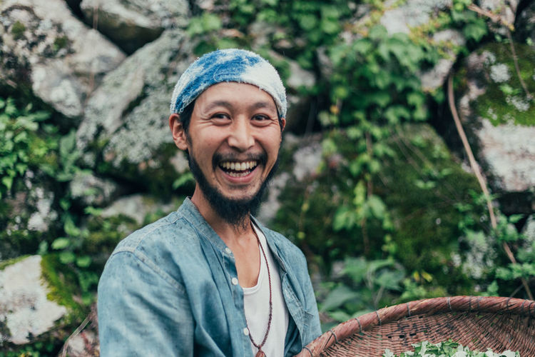 Portrait of smiling man holding basket while standing against rocks