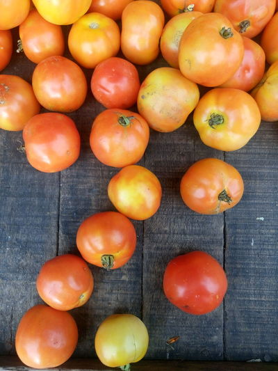 Directly Above Shot Of Tomatoes On Wooden Table At Market For Sale