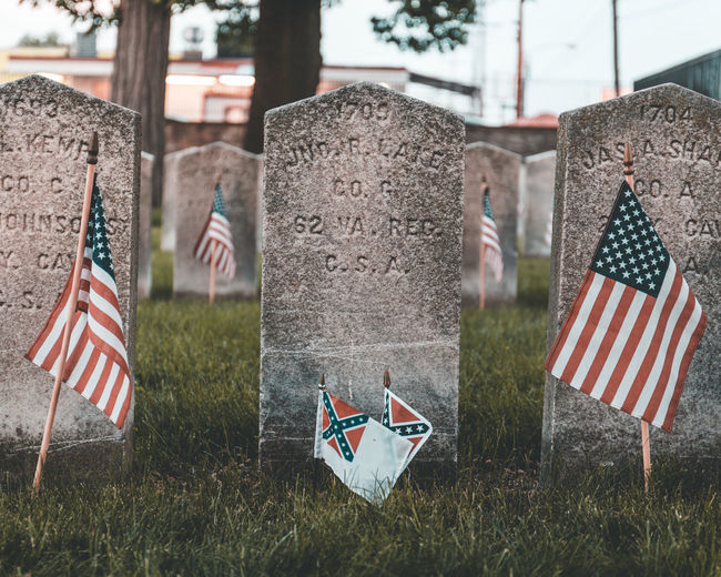 Cemetery Day Emotion Flag Grass Grave Memorial Nature No People Outdoors Patriotism Plant Shape Stone Tombstone War Memorial