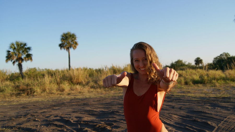 Portrait of cheerful young woman showing thumbs up at beach against clear sky