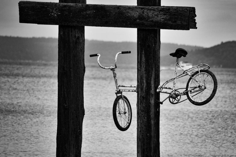 Close-up of bicycle on beach against sky