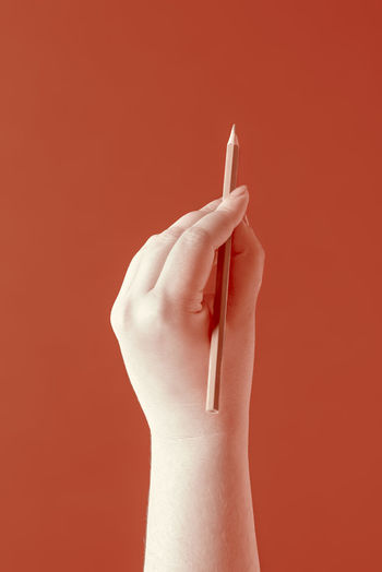 Close-up of hand holding ring against red background