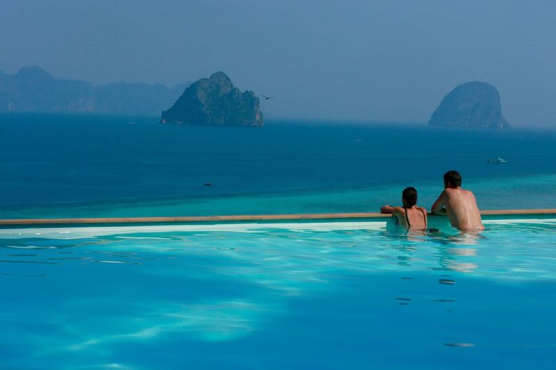 Rear view of couple in infinity pool in front of sea