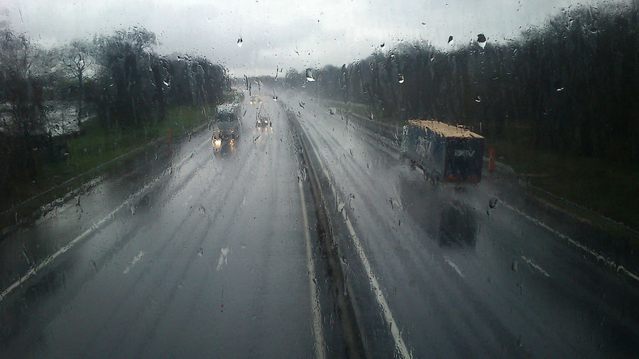 View of road seen through wet window