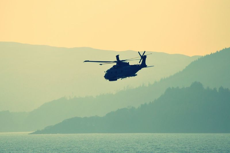 Silhouette Military Helicopter Flying Over Lake Against Mountains