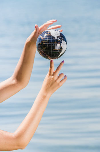 Hands of a young woman balancing the Earth on her finger - water ball showing various continents Earth EyeEmNewHere World In My Hands Balancing Ball Blue Close-up Continents Day Focus On Foreground Globe Holding Human Hand Leisure Activity Lifestyles Nature One Person Outdoors People Real People Sea Water Women World