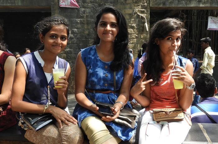 India Mumbai Bonding Casual Clothing Cheerful Communication Day Enjoy Drinking Friendship Front View Happiness Leisure Activity Lifestyles Looking At Camera Outdoors Portrait Real People Sitting Smiling Standing Store Togetherness Young Adult Young Women