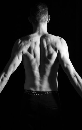 Rear view of shirtless man standing against black background