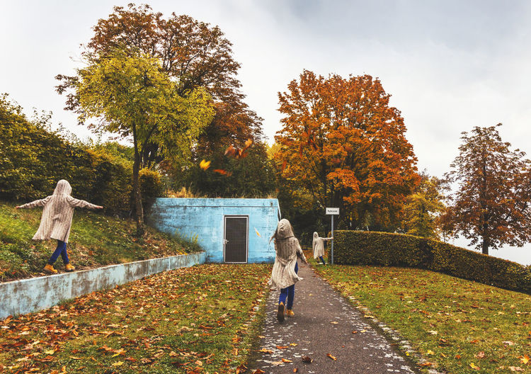 Boy walking on footpath by autumn trees against sky