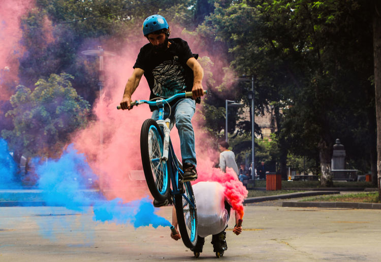 Adult Adults Only Celebration Day Full Length Headwear Helmet Holi Leisure Activity Lifestyles Men Motion Outdoors People Performance Real People Riding Speed Sport Togetherness Transportation Tree Two People Young Adult Young Men