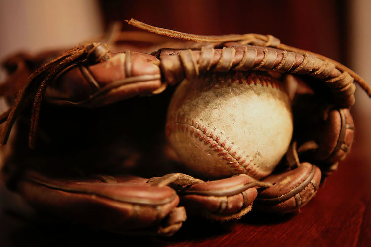 Close-up of baseball glove with ball on table