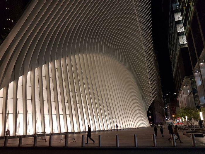 People walking in modern building at night