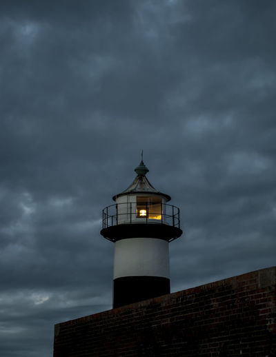 Low Angle View Of Illuminated Lighthouse Against Cloudy Sky