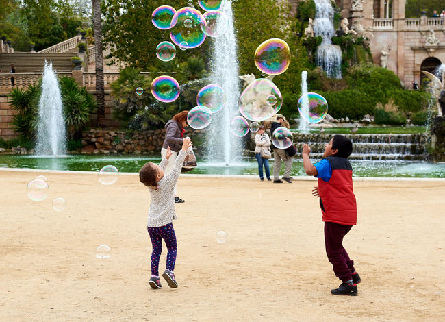 Children catching the soap bubbles in the in the Ciutadella Park in Barcelona. Ciutadella park is one of the finest parks in Barcelona. Park dotted with historic landmarks, statues and fountains Active Barcelona, Spain Catalonia Childhood Children City Ciutadella Park Crowd Of People Day Entertainment Europe Famous Place Fountain Fun Human Landmark Motion People Show Soap Bubbles SPAIN Spring Tourist Tourist Attraction  Travel Destinations