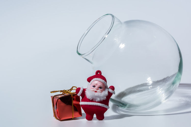 Christmas decoration and glass container over white background
