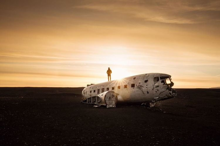 Man Standing On Abandoned Airplane Against Sky During Sunset