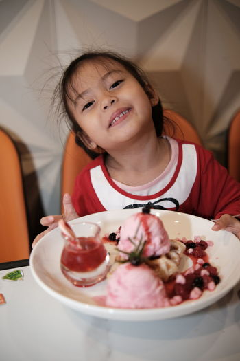 Portrait of a kid with strawberry ice cream in plate