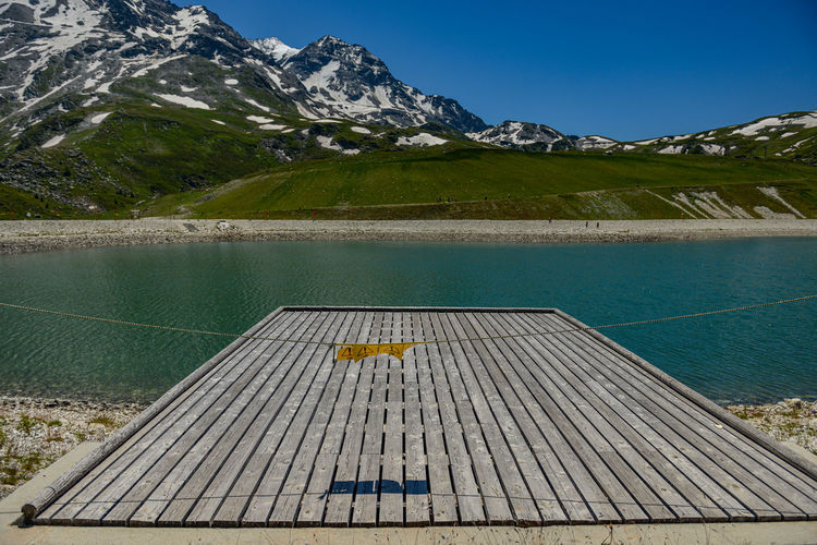 View of wooden ramp by lake against mountain