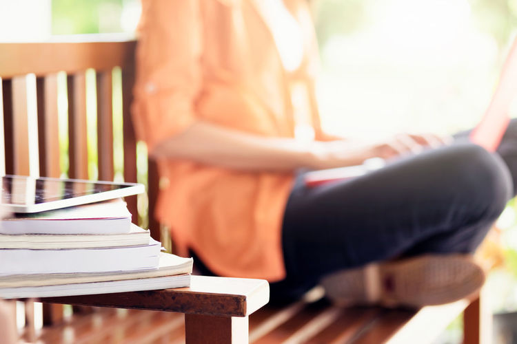 Stacked books by women sitting on bench