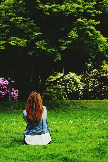 Rear view of girl standing on grassy field in park
