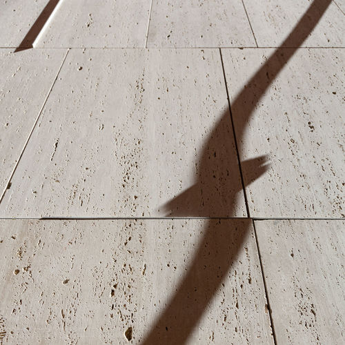 High angle view of shadow on tiled floor