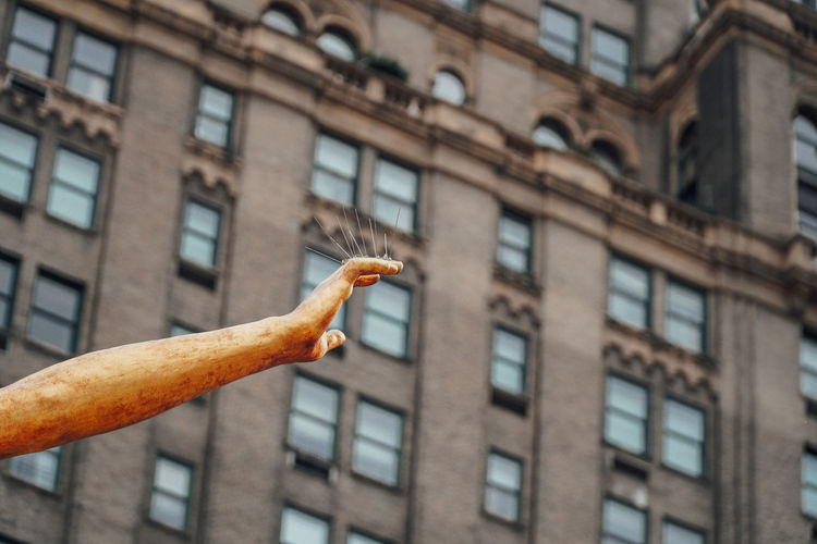 Low angle view of statue hand on building