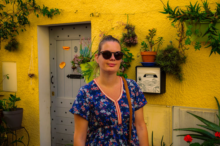 Young woman wearing sunglasses standing by house against building