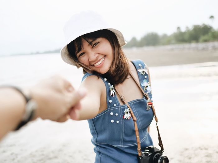 Cropped Hand Holding Cheerful Young Woman At Beach
