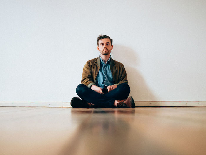 Full Length Portrait Of Serious Man Sitting On Hardwood Floor Against White Wall