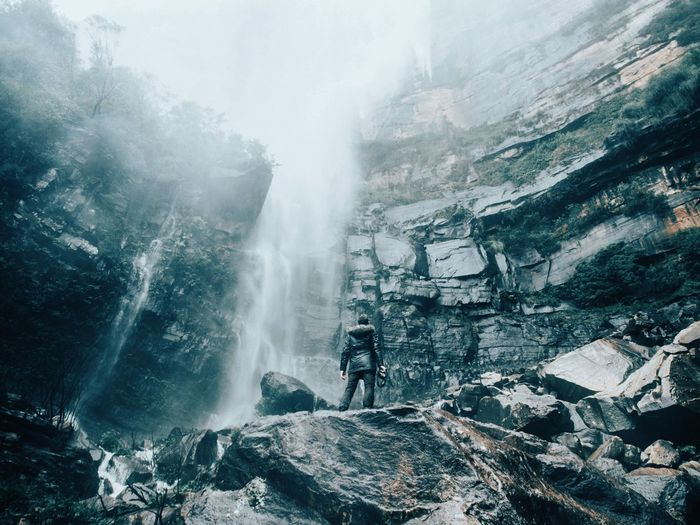 Woman standing on rocks while looking at waterfall