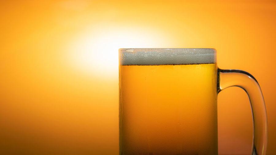 Close-up of beer glass against orange background