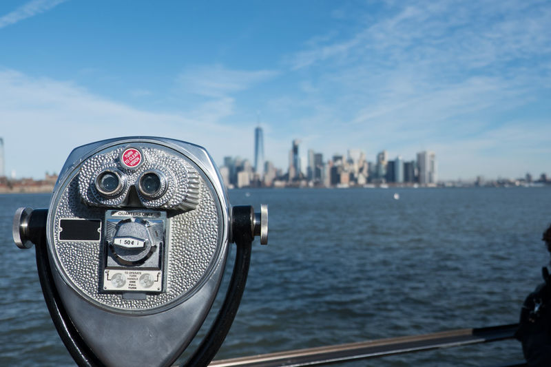 Tower viewer binoculars in foreground blurred New York City skyline in background overlooking Hudson River and the New York Harbor on a bright sunny day. Blue skies and wispy clouds over Manhattan. Ellis Island  Hudson River Hudson River Ny Liberty Island Manhattan Manhattan New York Manhattan Skyline Manhattan, New York City New York City New York City Photos New York Harbor New York Skyline  New York ❤ New York, New York Sightseeing Statue Of Liberty Statue Of Liberty New York Tower Viewer