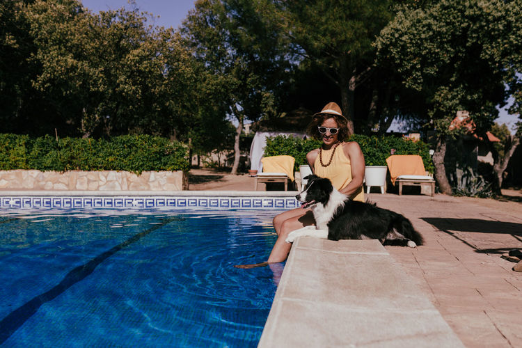 Woman with dog on swimming pool
