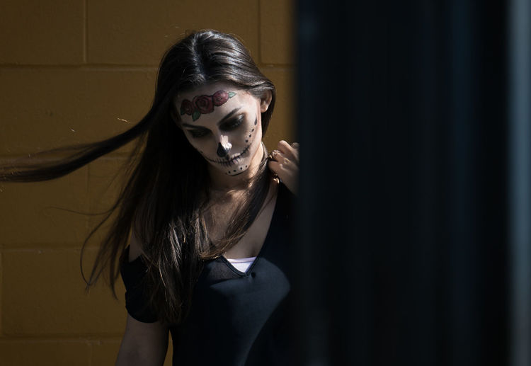 Woman with spooky halloween make-up standing against wall