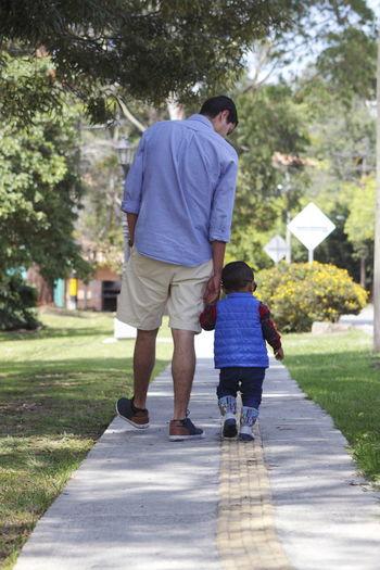Man and boy walking on footpath