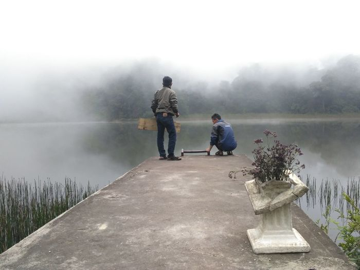 Friends On Pier Over Lake Against Sky During Foggy Weather