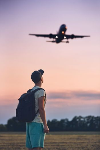 Young man (traveler) against moody sky with landing airplane. Freedom Landing Man Moody Sky Plane Tourist Transportation Travel Vacations Airplane Airport Aviation Backapacking Backpack Carefree Journey Lifestyles One Person People Real People Sky Summer Sunset Tourism Young Adult