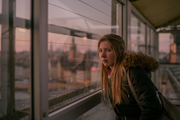 sunset in Stockholm Stockholm Sunset Sunset_collection Portrait Portrait Of A Woman Portrait Photography Girl Reflection City Young Women Beauty Beautiful Woman Women Looking Through Window Window Sky Thoughtful Warm Clothing This Is Natural Beauty Autumn Mood