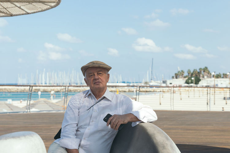 Portrait of senior man sitting on chair at harbor