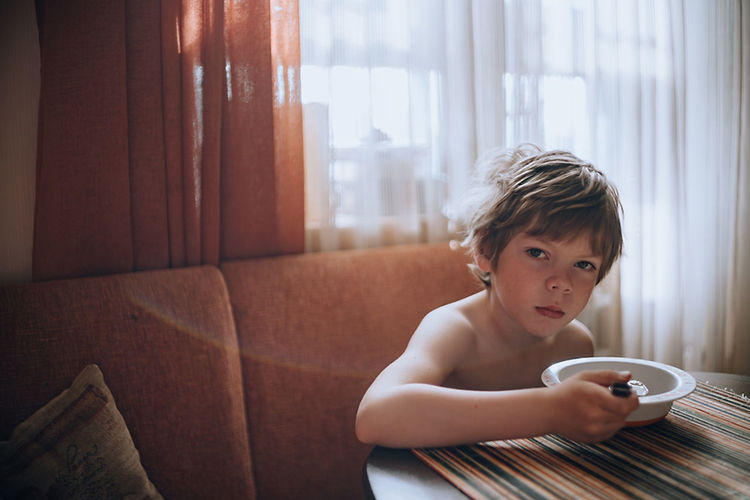 Little boy having breakfast in the kitchen One Person Portrait Indoors  Boys Child Looking At Camera Sitting Childhood Lifestyles Shirtless Home Interior Males  Real People Looking Leisure Activity Day Table Innocence Morning Light Breakfast
