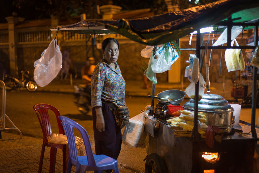Cambodia Street Market Bynight Casual Clothing Day Full Length Lifestyles Market Stall Marketplace Night One Person Outdoors People Phnompenh Real People Streetfood Three Quarter Length Working Young Adult