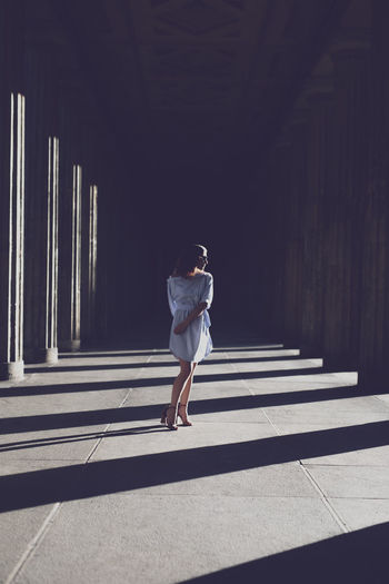 Woman standing at colonnade
