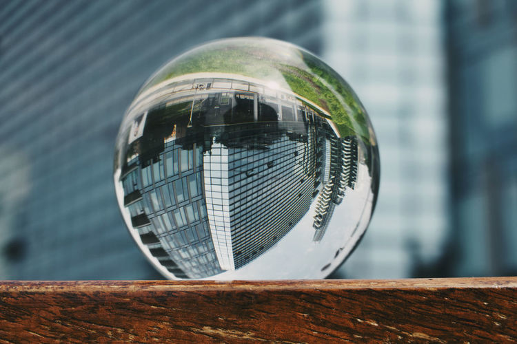 Close-up of crystal ball against building in the city