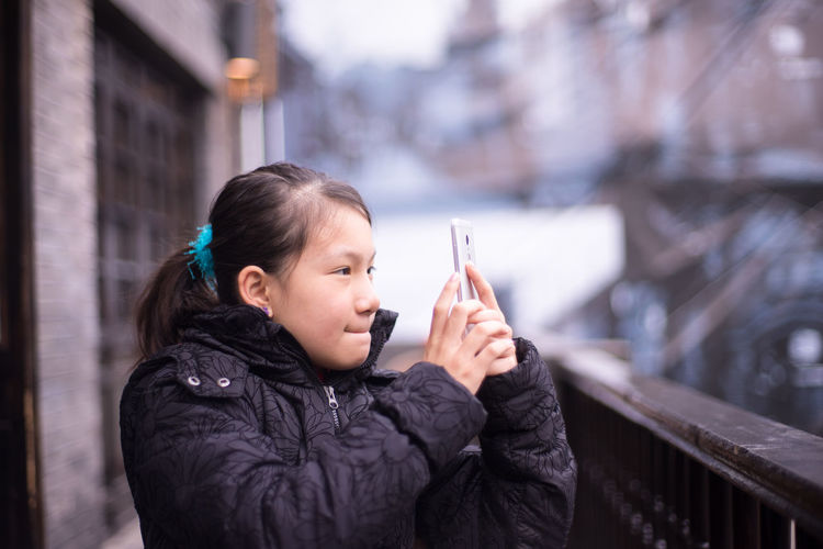 Girl tuning face expression for selfie. Black Cloth Buildings Chinese Style Cute Face Expression Girl Lovely Self-portrait Selfie Smart Phone Winter