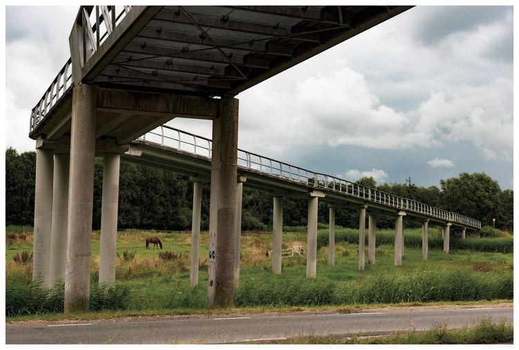 Bridge over road amidst field against sky