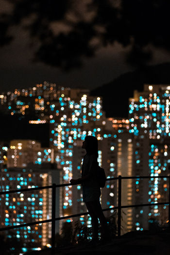 Rear view of silhouette man standing against illuminated buildings in city